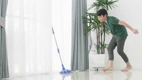 清洗房子的亚洲年轻男孩帮助家庭使用拖把 股票视频