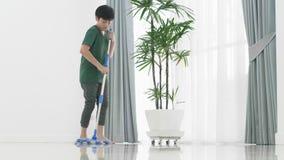 清洗房子的亚洲年轻男孩帮助家庭使用拖把 股票录像