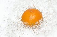 清洗新鲜的水多的橙色飞溅水 免版税库存图片