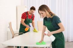 清洗桌的专业管理员在办公室 免版税库存图片