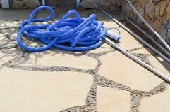 清洗水池洗涤和浇灌的植物蓝色塑料长的大波纹状的水管 图库摄影
