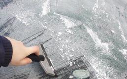 清洗汽车玻璃从冰和雪玻璃 库存照片
