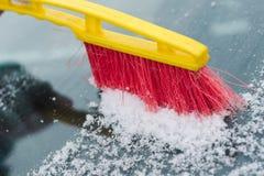 清洗汽车的挡风玻璃的过程从雪与一把红色和黄色刷子 免版税库存图片