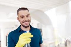 清洗窗口的橡胶手套的人与浪花 免版税库存照片