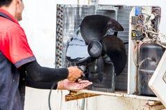 清洗老空调器的肮脏的压缩机技术员固定在救球能量的肮脏的墙壁背景 库存照片
