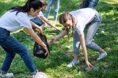 清洗草坪的年轻志愿者 库存照片