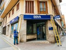 清洗西班牙BBVA的门面的工作者 库存图片