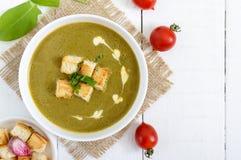 清淡的素食主义者菠菜奶油汤用在一个碗的酥脆油煎方型小面包片在白色背景 免版税图库摄影