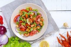 清淡的鲜美沙拉用癌症的肉,虾,莴苣,大蒜油煎方型小面包片,蕃茄,在白色背景的红洋葱 库存照片