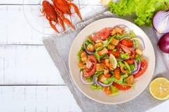 清淡的鲜美沙拉用癌症的肉,虾,莴苣,大蒜油煎方型小面包片,蕃茄,在白色背景的红洋葱 免版税库存图片