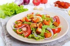 清淡的鲜美沙拉用癌症的肉,虾,莴苣,大蒜油煎方型小面包片,蕃茄,红洋葱 免版税库存照片