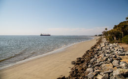 清疏的船在离岩石防波堤的附近海岸  免版税库存照片