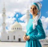 清真寺背景的年轻回教女孩 库存图片