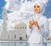 清真寺背景的年轻回教女孩 免版税库存图片