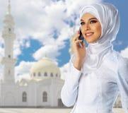 清真寺背景的年轻回教女孩 免版税图库摄影