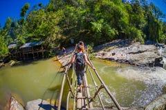 清莱,泰国- 2018年2月01日:使用一个木桥的未认出的人民穿过一条小河  免版税库存照片