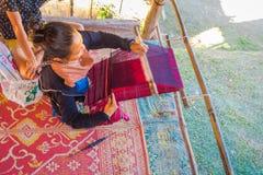 清莱,泰国- 2018年2月01日:在编织传统泰国织品,在城镇的观点的未认出的妇女上 图库摄影