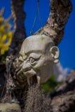 清莱,泰国- 2018年2月01日:垂悬从树的雕刻的石头在Wat荣Khun,白色寺庙  库存照片