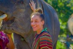 清莱,泰国- 2018年2月01日:摆在接近在密林圣所的一头大象的美丽的妇女画象 库存图片