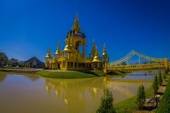 清莱,泰国- 2018年2月01日:有一座桥梁的美丽的金黄寺庙在湖, Wat Suan Dok修道院 免版税库存图片