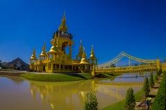 清莱,泰国- 2018年2月01日:有一座桥梁的美丽的金黄寺庙在湖, Wat Suan Dok修道院 免版税图库摄影