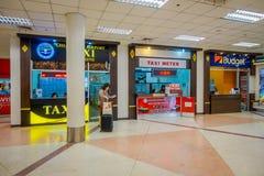 清莱,泰国- 2018年2月01日:有她的lugage的未认出的妇女接近出租汽车柜台,里面  免版税库存照片