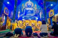 清莱,泰国- 2018年2月01日:祈祷在他们的在一个巨大的菩萨雕象前面的膝盖的未认出的人民  库存图片