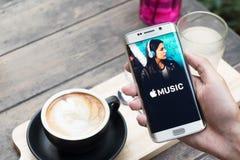 清迈,泰国- 2015年11月20日:拿着苹果计算机音乐app的屏幕快照人手显示在三星星系s6边缘 苹果计算机Mu 库存照片