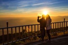 清迈,泰国- 2016年1月17日:结合采取与智能手机的selfie画象在山背景在日落 土井Int 免版税库存照片