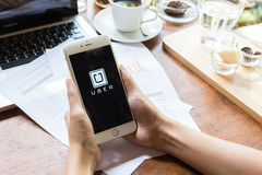 清迈,泰国- 5月09,2015 :举行Uber app的妇女手显示在iphone 6个加号在咖啡店, Uber是智能手机appb 图库摄影