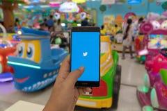 清迈,泰国- 1月22 :卡伦小山部落坐她的小屋在卡伦2010年1月22日的小山村庄在清迈,泰国 06,2019:举行有Twitter应用程序的人华为在屏幕上 Twitter是一网上新闻和社会的 免版税图库摄影