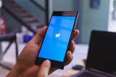 清迈,泰国- 2月13,2018:拿着有Twitter商标的人手索尼xperia xzs手机在屏幕上 Twitter是  免版税图库摄影
