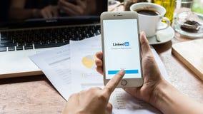 清迈,泰国09 2016年:举行iPhone的女商人与社交网路服务LinkedIn的6个加号在屏幕上 iPho 免版税库存图片