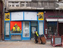 清道夫在街道上的倒垃圾工人有被放弃的商店的在布达佩斯 库存图片