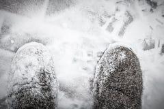 清除与雪铁锹的随风飘飞的雪老妇人的腿 o 免版税库存照片