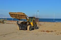 清除海滩的一台挖掘机 免版税库存照片