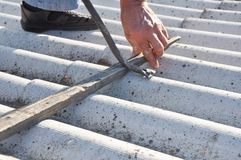 清除石棉 盖屋顶的人石棉安全处理和撤除  屋顶建筑 免版税库存图片