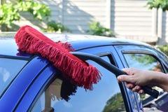 清洗一辆蓝色汽车的人 图库摄影