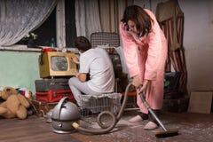 清洗一间被放弃的屋子的年轻夫妇 库存图片