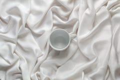 清洗在丝绸白色织品的陶瓷空的咖啡杯 顶视图 库存图片