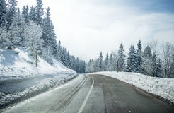 清洗在山与轮和曲线的冬天路与树联合国 免版税库存图片