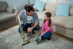 清洗地毯的女儿帮助的父亲与吸尘器 库存图片