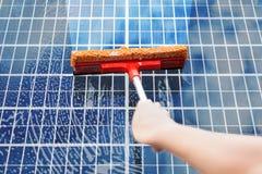 清洗太阳电池板的人 免版税库存照片