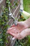 清洗她的手的妇女在庭院里 免版税库存图片