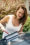 清洗她的汽车的挡风玻璃妇女 免版税库存图片