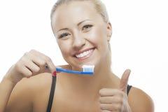 清洗她的牙的愉快的白肤金发的白种人妇女画象与 免版税库存图片