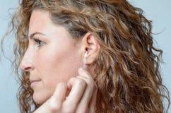 清洗她的耳朵的妇女与棉花棒 免版税库存图片