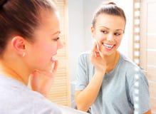 清洗她的面孔的秀丽女孩与化装棉 免版税库存照片