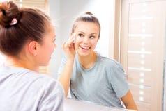 清洗她的面孔的秀丽女孩与化装棉 库存图片