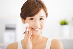 清洗她的面孔的美丽的亚裔少妇与棉花 免版税库存图片